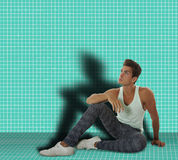 Man sitting in a room on the ground. Man sitting in a room with tiles on the ground. He is lonely and is thinking. His shadow is projected on the wall Stock Photography