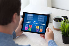Man sitting in room and holding tablet with app smart Stock Images