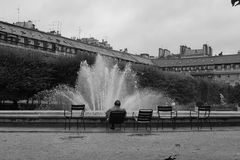 Man sitting at Royal Palace Gardens Royalty Free Stock Photography