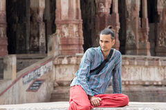 A man is sitting among the ruins. A man in red pants sits among the ruins of the ancient city of Vijayanagar Stock Image