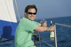 Man sitting on sailboat, drinking white wine Royalty Free Stock Photography