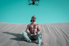 Man Sitting on Sand Controlling Drone stock images