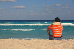 The man sitting on the sand by the sea Stock Photos