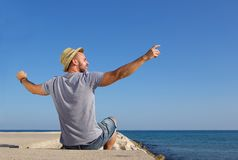 Man sitting by the sea with arms spread open Stock Photography