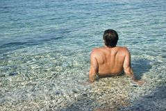 Man sitting in the sea and relaxing. Stock Image