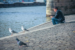 A man sitting by  the Seine embankment in Paris Stock Images