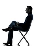 Man sitting side view silhouette full length. One man sitting looking up full length in silhouette studio isolated on white background royalty free stock image