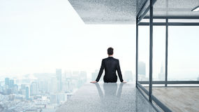 Man sitting on skyscrapper Royalty Free Stock Image