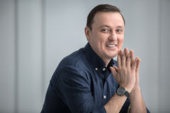 Man sitting with a slight smile and looking at the Royalty Free Stock Photos