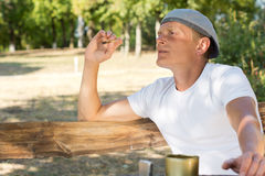 Man sitting smoking in the park Royalty Free Stock Image