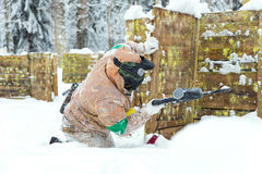 Man sitting on snow behind wooden fortification playing paintbal. L Stock Photography