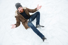 Man sitting on the snow in ice skates Royalty Free Stock Photo