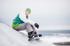 Man sitting on the snow with snowboard Stock Images