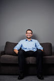 Man sitting on sofa Stock Images