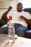Man Sitting On Sofa With Bottle Of Vodka And Cigarettes Royalty Free Stock Images