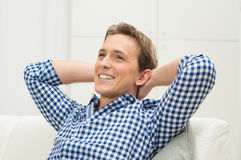 Man Sitting On Sofa Contemplating. Happy Young Man With Hand Behind Head Contemplating Royalty Free Stock Photos
