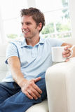 Man Sitting On Sofa Drinking Coffee Relaxing At Ho Stock Photo