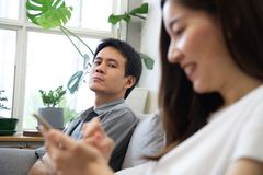 A Man sitting on sofa is feeling unhappy with his girlfriend. His girlfriend because she spent too much time on the phone. Social problem of family relationship royalty free stock photos