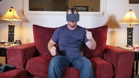 Person at Home Uses a Virtual Reality Heads Up Glasses Unit. 7830 A man sitting on a sofa in his home uses a virtual reality heads up unit stock video footage