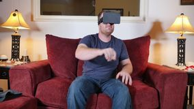 Young Man at Home Uses an Augmented Reality Heads Up Unit. A man sitting on a sofa in his home uses a virtual reality heads up unit stock video footage