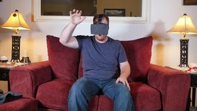 Young Man at Home Uses a Virtual Reality Heads Up Unit. A man sitting on a sofa in his home uses a virtual reality heads up unit stock video footage