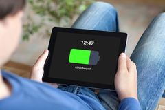 Man holding tablet with charged battery on screen Stock Images