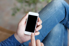 Man sitting on a sofa and holding a white touch phone with a bla Stock Image