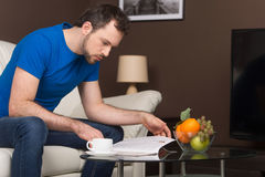 Man sitting on sofa in home and reading. Royalty Free Stock Images