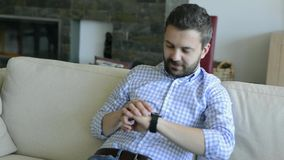 Man sitting on sofa at home using smart watch stock video footage