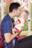 Man sitting on sofa while kissing his baby. Portrait of happy father sitting on couch while holding and kissing his baby near the window at home Stock Photos