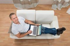 Man Sitting On Sofa With Laptop royalty free stock photo
