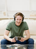 Man sitting on sofa and listening to music Stock Images