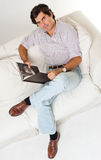 Man sitting on a sofa reading a book Royalty Free Stock Photos