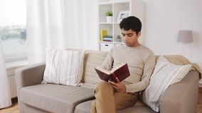 Man sitting on sofa and reading book at home stock video