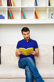 Man sitting on sofa and reading the book Royalty Free Stock Images