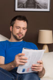 Man sitting on sofa relaxed and reading magazine. Royalty Free Stock Image