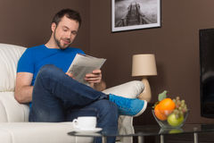 Man sitting on sofa relaxed and smiling. Royalty Free Stock Photos