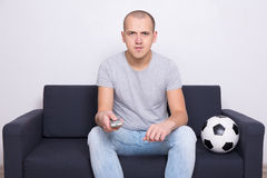 Man sitting on sofa with soccer ball and watching tv at home Royalty Free Stock Photography