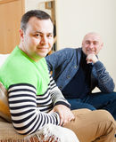 Man sitting on sofa. Two adult men resting at home stock photos