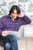 Man sitting in sofa using electronic tablet Stock Photos