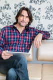 Man sitting in sofa using electronic tablet Royalty Free Stock Photos