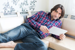 Man sitting in sofa using electronic tablet Royalty Free Stock Image