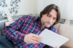 Man sitting in sofa using electronic tablet Royalty Free Stock Images