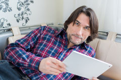 Man sitting in sofa using electronic tablet Stock Photography