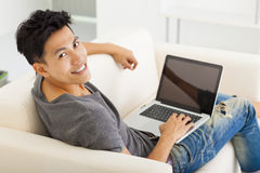 Man sitting in sofa and using  laptop Stock Image