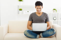 Man sitting in sofa and using  laptop Stock Photo