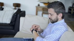 Man sitting on sofa using smartphone and smart watch stock video