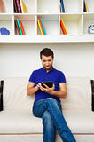 Man sitting on sofa and using tablet pc Stock Images