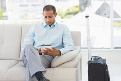Man sitting on sofa waiting to depart on business trip Royalty Free Stock Images