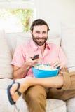 Man sitting on sofa watching television Royalty Free Stock Image